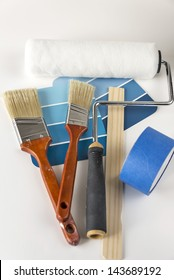 A collection of house painting supplies that includes a roller, paint brushes, paint samples, paint stir stick and painters tape. Copy space was provided and selective focus was used on this image.