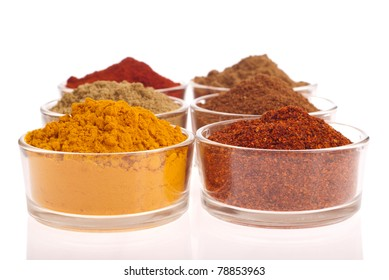 collection of indian spices (cumin, coriander, paprika, garam masala, turmeric, chili powder) on glass cups isolated on white background