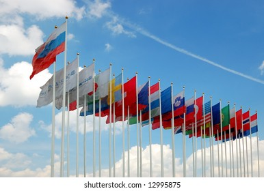 Collection of international flags over a cloudy blue sky