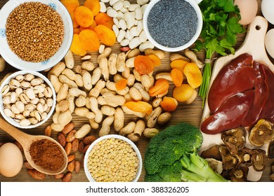 Collection iron rich foods as liver, buckwheat, eggs, parsley leaves,dried apricots, cocoa, lentil, bean, blue poppy seed, broccoli, dried mushrooms, peanuts and pistachios on wooden table.