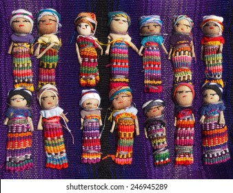 A collection of large, colorful Guatemalan Worry Dolls lined up in two rows on a purple woven blanket.