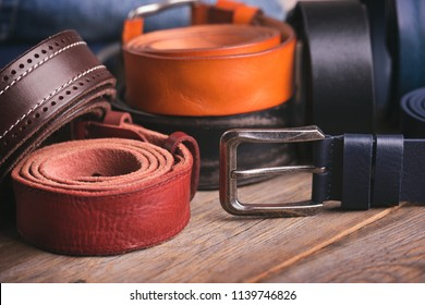 Collection of leather belts on a wooden table