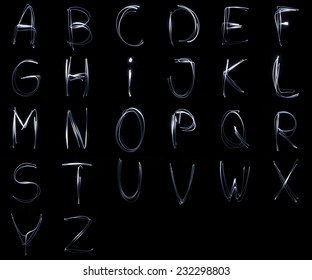 Collection of letters written with a flashlighgt isolated on black background