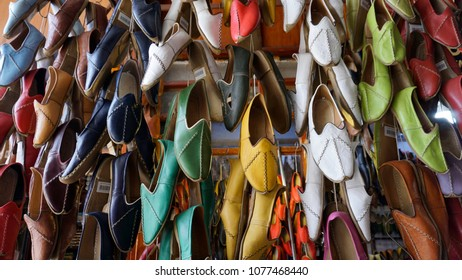 Collection of lots of traditional colorful shoes in the bazaar or market at Gaziantep City, Turkey. Colorful shoes texture pattern background. Variety of the colorful leather shoes in the shop.
