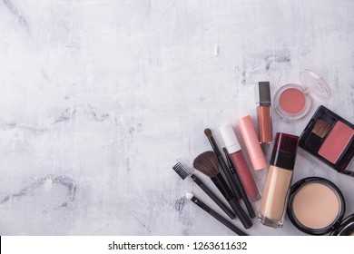 A collection of make up and beauty products arranged on white wooden background with empty space.