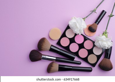 collection of make up and cosmetic beauty products arranged on pink background
