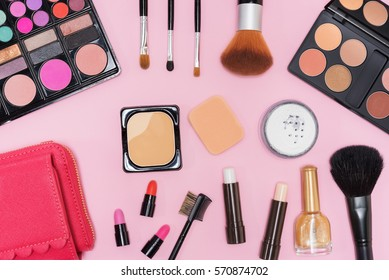 Collection of makeup cosmetics palette, lipstick and brushes on pink background flat lay top view