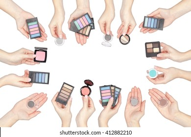 collection of makeup products in a hands isolated on white background