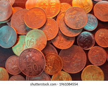 Collection of malaysian coins with light yellow, wooden background. Contains 10 cent, 20 cent and 50 cent coins.