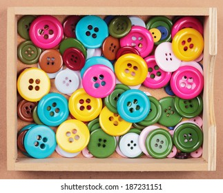 a collection with many buttons of different colors and sizes in a box