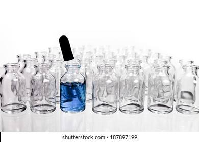 A collection of many small empty scientific vials in rows with a single eye-dropper in one of the containers.