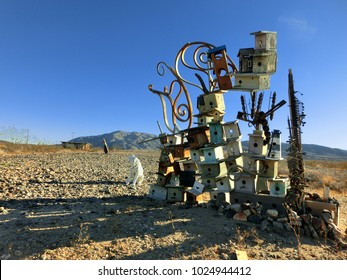 Collection of many stacked wooden birdhouses abandoned in desert