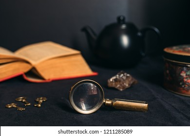 Collection of mysterious objects on a black background: book, keys, magnifying glass, crystal, box and teapot.