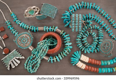 "A collection of Native American Jewelry.A Santo Domingo Depression Era� Necklace, and Turquoise ""Nugget"" with silver beads, and Zuni and Navajo ""Cuff"" Bracelets, on a Grey Slate Background."