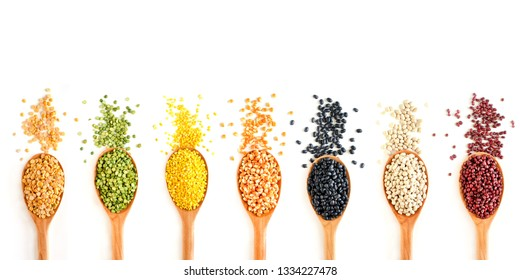 Collection of natural cereal food consisted of soybean,mung bean,dry corn,black bean,kidney,and small white bean seed,in wooden spoon on white background
