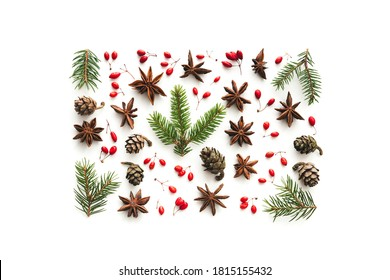 Collection of natural Christmas ornaments (cone, pine twigs, red berries, anise stars) isolated on white. Flat lay. View from above.