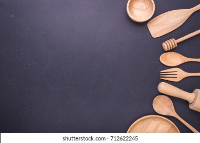 Collection of new wooden kitchen utensil, bowl, plate, spoon, dish. Studio shot on black table background. With free space for text or design