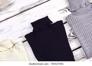 Collection of new wool turtlenecks. New folded knitted turtleneck sweaters for kids, old wooden bakground. Winter casual knitwear.