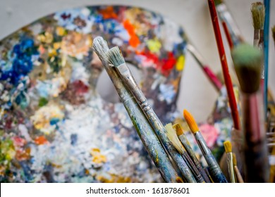Collection of oil paint brushes with artist palette in background
