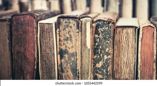 Collection of old, aged books in a row. Leather hardcover manuscripts.