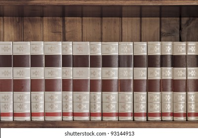 Collection of old books. Could be encyclopedias, concordances, series etc. Sitting on a beautiful wooden book shelf.