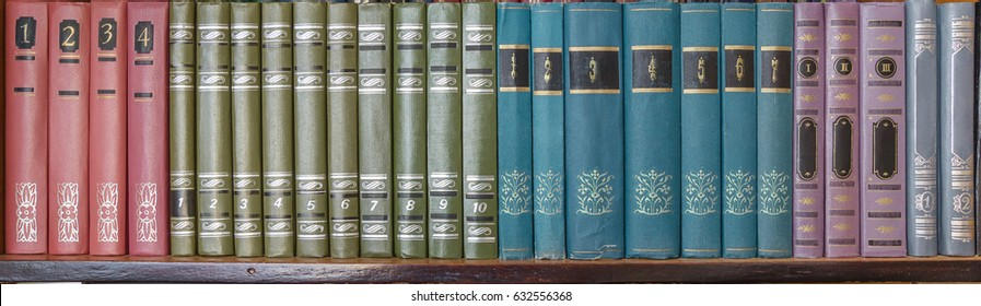 Collection of old books lined up on bookshelf