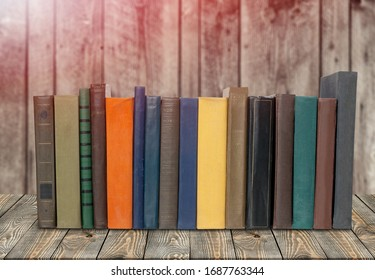Collection of old books on a wooden desk