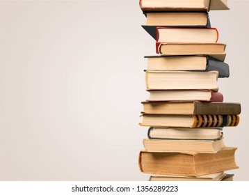 Collection of old books vertical stack on beige background
