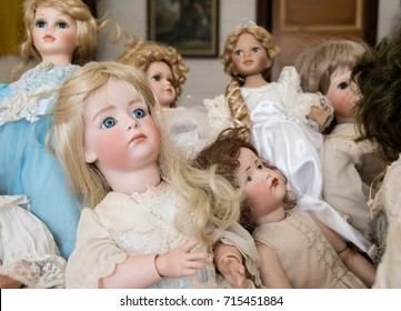 Collection of old porcelain dolls placed on bed