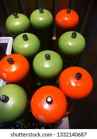 A collection of orange and green pepper grinders as a background