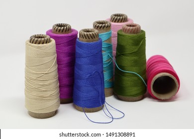 a collection of partly used weaving yarn (5/2 mercerized cotton) in bright colours - purple, pinks, blues, green and fog.  off-white background