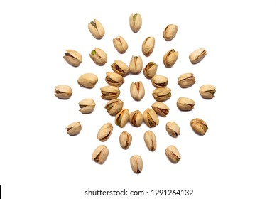 A collection of pistachio nuts lie in the shape of a circle or sun on an isolated white background. with clipping path. Pistachio pattern
