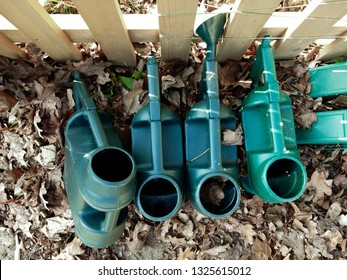 A collection of plastic green watering cans in a garden