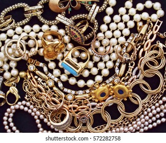 a collection of  precious golden jewels on black velvet background