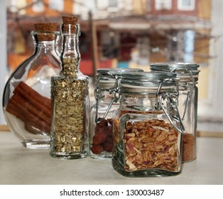 A collection of pretty bottles and jars containing a variety of herbs and spices in a window sill.