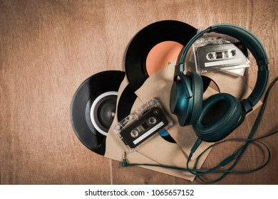 Collection of retro audio tapes and old vintage vinyl record on wooden table. Top view of audio cassettes, headset and gramophone record or old vinyl record.