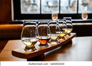 Collection of Scottish whisky, tasting glasses with variety of single malts or blended whiskey spirits on distillery tour in Scotland, UK