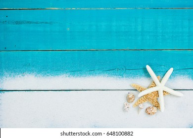 Collection of seashells and starfish in sand border on antique rustic teal blue wood background; blank wooden beach sign with copy space