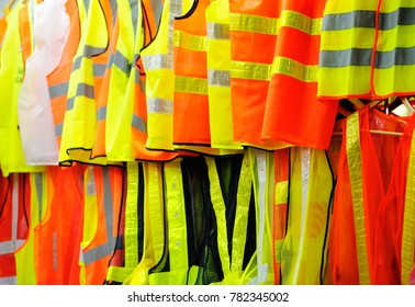 Collection of security reflective cloths, orange and yellow, hanging in row.vests.