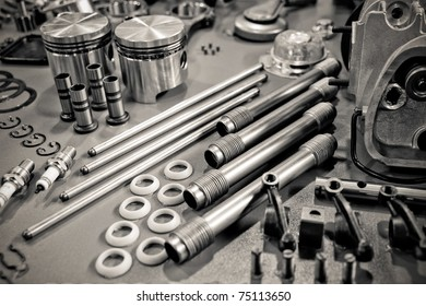 collection of sepia toned precision auto engine parts laid out in a workshop