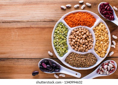 collection set of beans, legumes, peas, lentils on ceramic bowl on wooden background