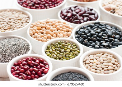 collection set of beans, legumes, peas, lentils on ceramic bowl on white wooden background