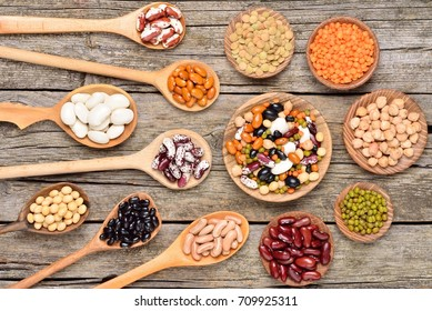 Collection set of natural beans, legumes, peas, lentils in wooden utensils on wooden background. Copyspace background. Top view.