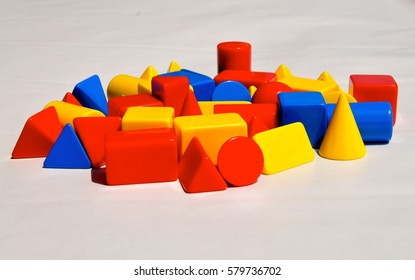 A collection of shiny, plastic 3 dimensional shapes in the primary colours or red, yellow and blue in a random arrangement.