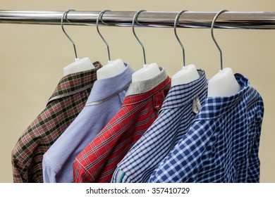 Collection of shirts hanging in row on hangers in store closeup