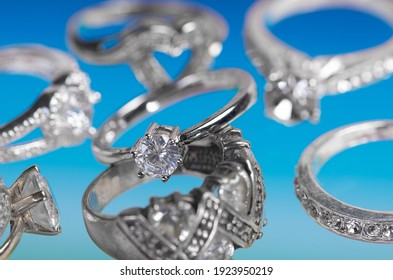 Collection of silver rings on a blue background.