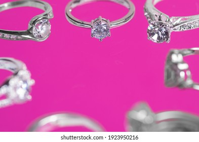 Collection of silver rings on a pink background.