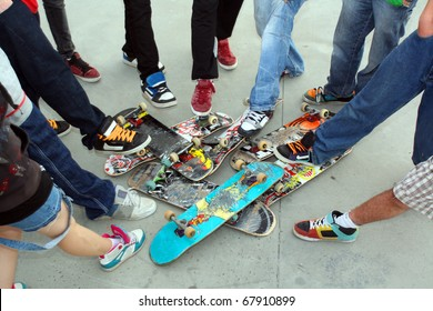 A collection of Skate boards and their owner's legs and feet at Limerick City Skate Park