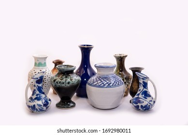 Collection of Small decorated mud pots on white background