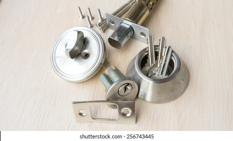 Collection of small parts to create a complete metal deadbolt lock on clean wooden surface